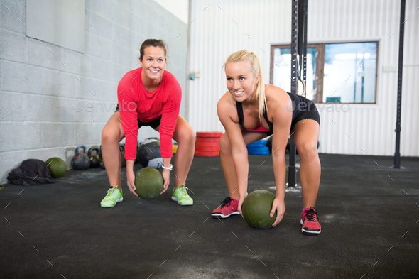 Determined Female Athletes Lifting Medicine Balls In Health Club - Stock Photo - Images