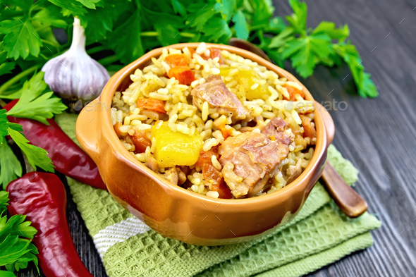 Rice with chicken and zucchini in bowl on board - Stock Photo - Images