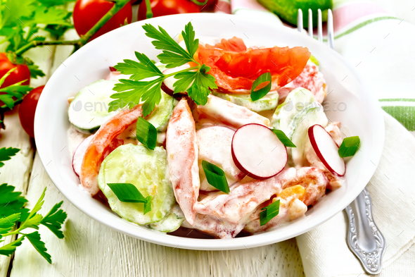 Salad from fresh vegetables and greens in plate on light board - Stock Photo - Images