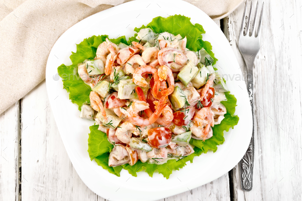 Salad with shrimp and avocado in plate on board top - Stock Photo - Images