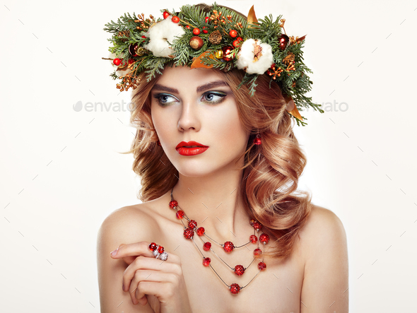 Portrait of beautiful young woman with Christmas wreath - Stock Photo - Images