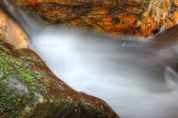 Abstract detail of flowing water between the boulders - Stock Photo - Images