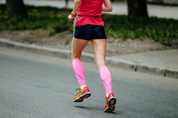 back runner girl in pink compression socks - Stock Photo - Images