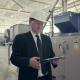 Businessman in Hard Hat Walking Through Factory