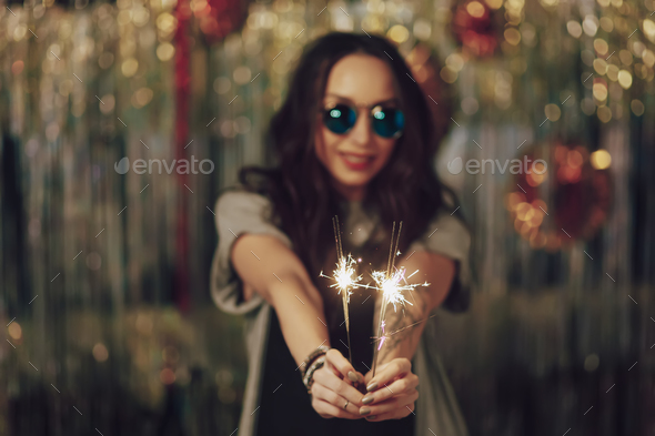 Focus on woman hands holding sparklers - Stock Photo - Images