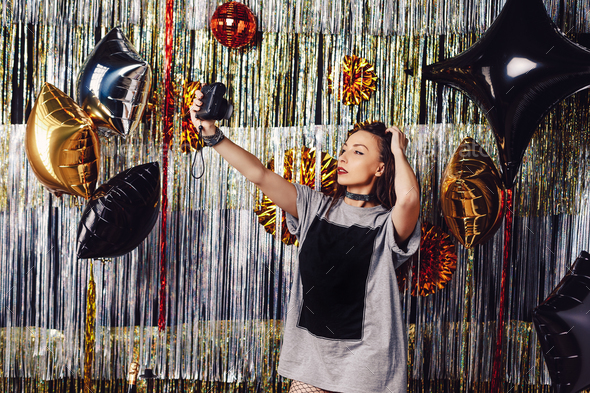 Party girl taking photo on sparkling background - Stock Photo - Images
