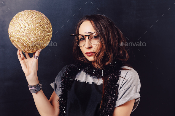 Portrait of seductive hipster girl holding a gold discoball - Stock Photo - Images