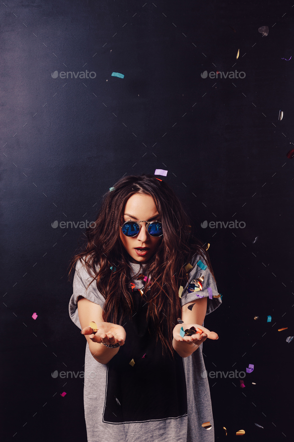 Surprised girl with confetti in hands - Stock Photo - Images