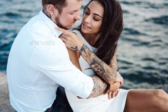 Young couple are sitting on the pier by the sea - Stock Photo - Images