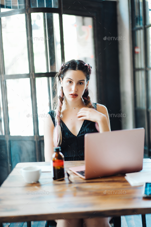 Young woman sitting in coffee shop - Stock Photo - Images