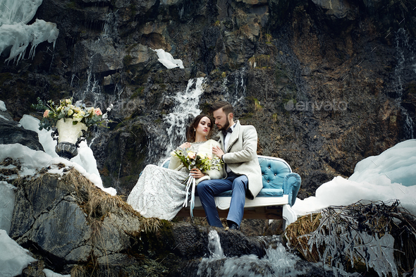 Happy couple hugging on rock on the background of nature - Stock Photo - Images