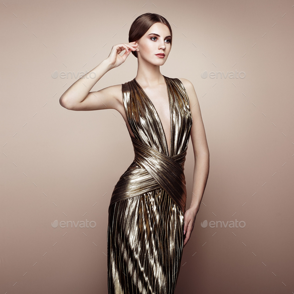 Fashion portrait of young beautiful woman in gold dress - Stock Photo - Images
