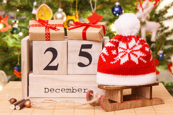 Date 25 December on calendar, gifts with sled and cap, christmas tree - Stock Photo - Images
