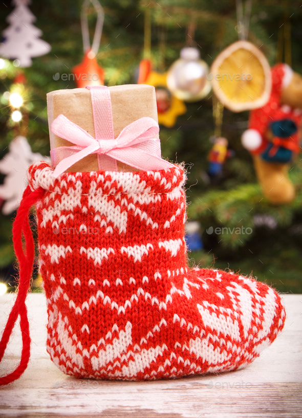 Wrapped gift with ribbon for Christmas in red sock on background of christmas tree with decoration - Stock Photo - Images