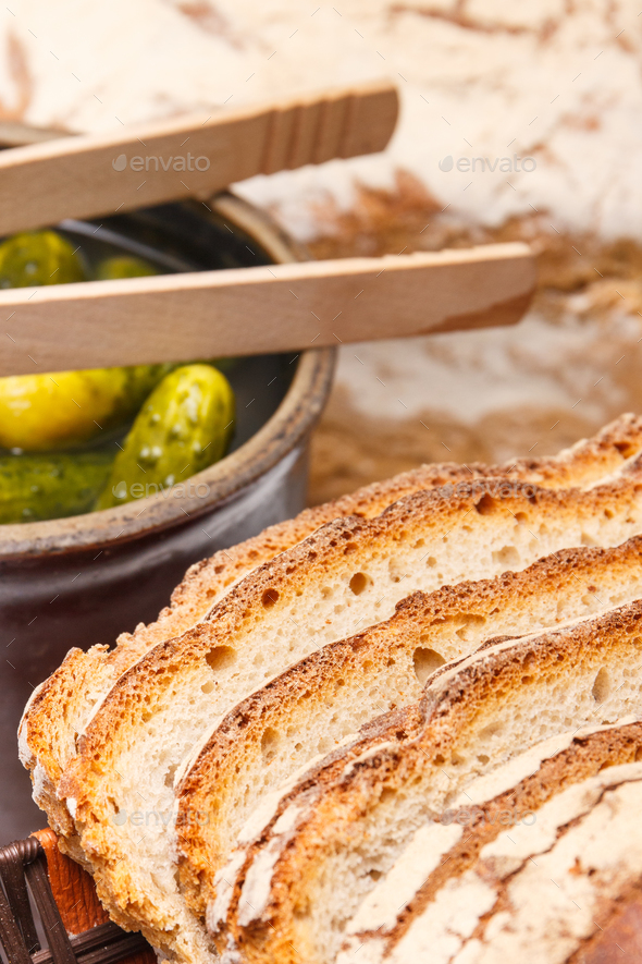 Slices of fresh baked loaf of rye or wheat bread and pickled cucumbers in clay pot - Stock Photo - Images