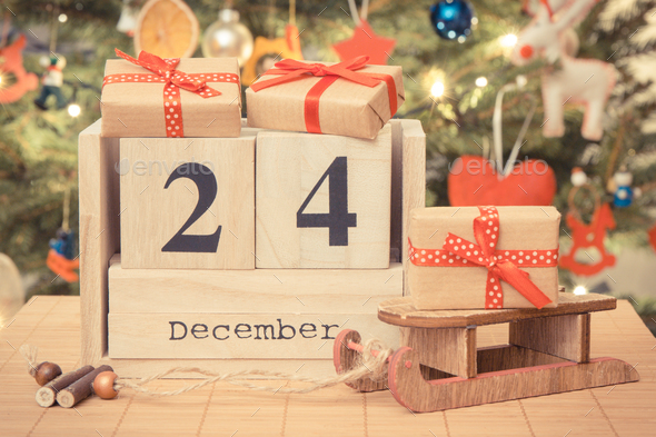 Date 24 December on calendar, wrapped gifts and christmas tree - Stock Photo - Images