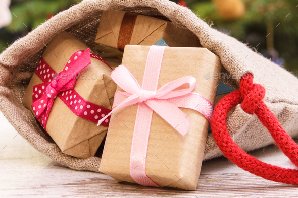 Heap of gifts with ribbons in bag for Christmas on background of christmas tree with decoration - Stock Photo - Images