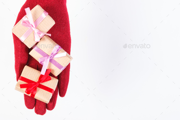 Hand of woman in gloves with gifts for Christmas or other celebration, copy space for text on white - Stock Photo - Images