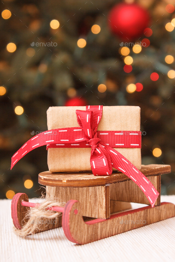 Wrapped gift with ribbonon wooden sled and christmas tree with lights in background - Stock Photo - Images