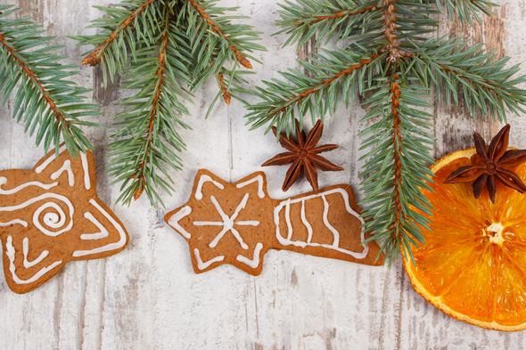 Fresh baked gingerbread, spruce branches and spices on old board, christmas decoration - Stock Photo - Images