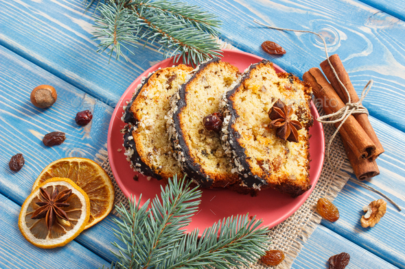Fresh baked fruitcake for Christmas on plate and spruce branches on blue boards - Stock Photo - Images