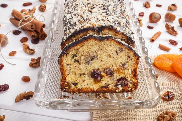 Fresh baked fruitcake with ingredients on white boards - Stock Photo - Images