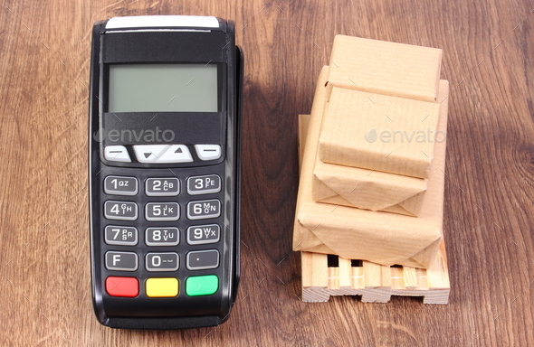 Payment terminal and wrapped boxes on wooden pallet, concept of paying for products and shipping - Stock Photo - Images