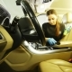 Young Woman in Blue Gloves Is Cleaning Interior of the Car for Luxury SUV