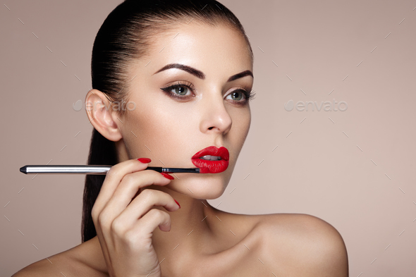 Beautiful woman paints lips with lipstick - Stock Photo - Images