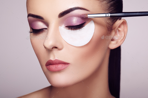 Makeup artist applies eye shadow - Stock Photo - Images