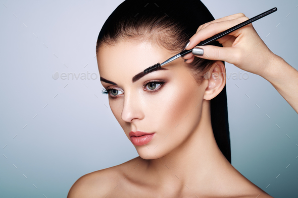 Beautiful brunette woman paints the eyebrows - Stock Photo - Images