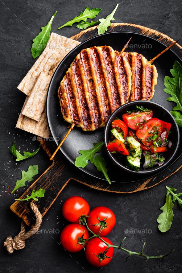Juicy grilled chicken meat lula kebab on skewers with fresh vegetable salad - Stock Photo - Images