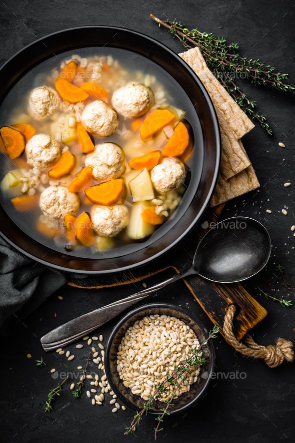 Fresh vegetable soup with meatballs and pearl barley in bowl on black background. Top view - Stock Photo - Images