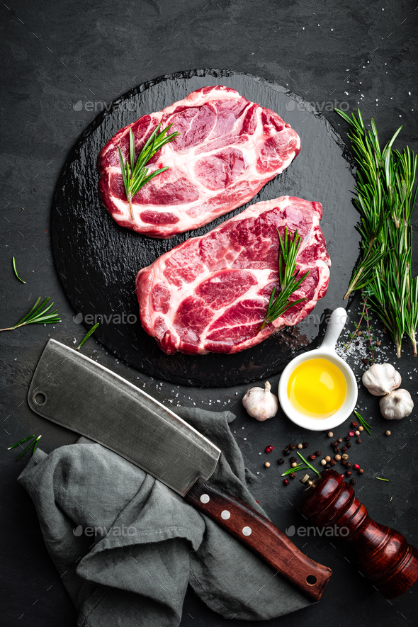 Cooking on kitchen table fresh raw pork marbled steaks on black background, top view - Stock Photo - Images