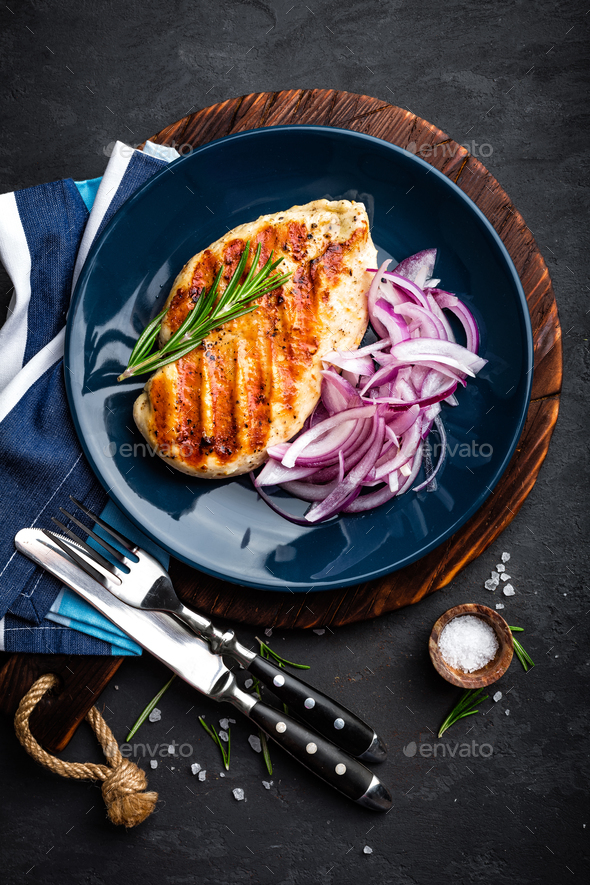 Juicy grilled chicken meat, fillet with fresh marinated onion on plate. Black background, top view - Stock Photo - Images