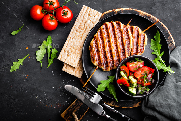 Juicy grilled chicken meat lula kebab on skewers with fresh vegetable salad on black background - Stock Photo - Images