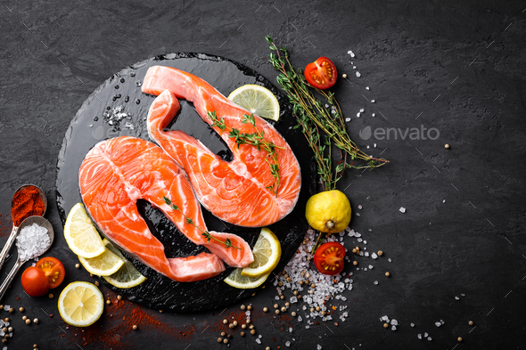 Fresh raw salmon red fish steaks on black background. Top view - Stock Photo - Images