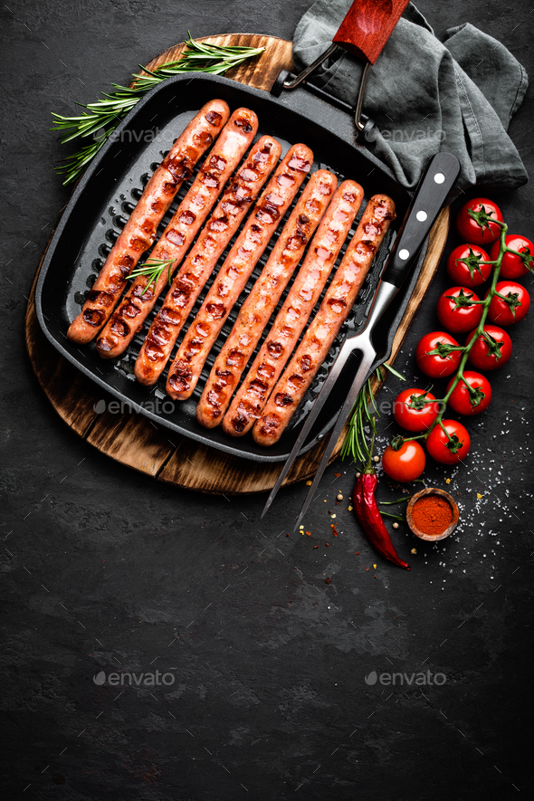 Grilled sausages bratwurst in grill frying-pan on black background. Top view - Stock Photo - Images