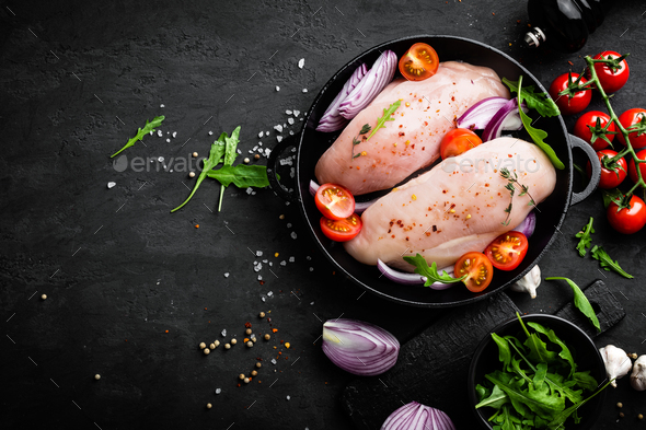Fresh raw chicken meat, fillet marinated with spices, onion and tomatoes on black background - Stock Photo - Images