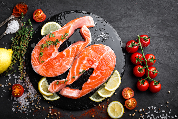 Fresh raw salmon red fish steaks on black background, top view - Stock Photo - Images