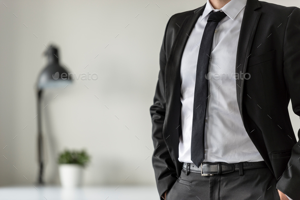 Business man in his office with his hands in the pockets of his - Stock Photo - Images