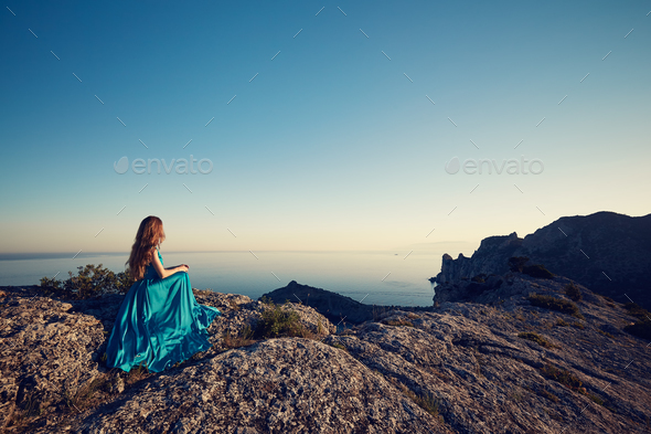 Young beautiful woman in blue dress looking to mountains sea - Stock Photo - Images