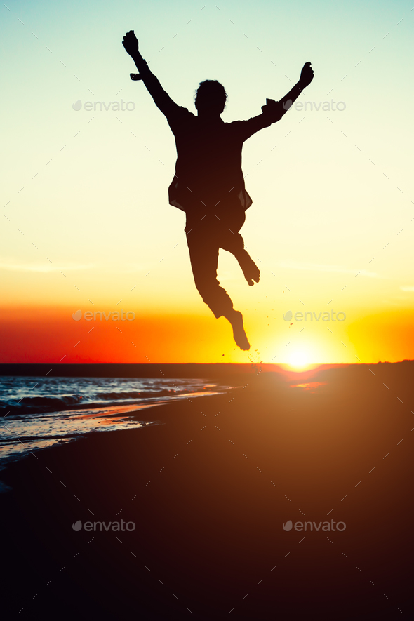 Silhouette young woman jumping with hands up on the beach at the - Stock Photo - Images