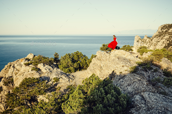 Young beautiful woman in red dress looking to mountains sea - Stock Photo - Images