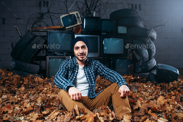 Stalker, mountain of old TVs on background - Stock Photo - Images