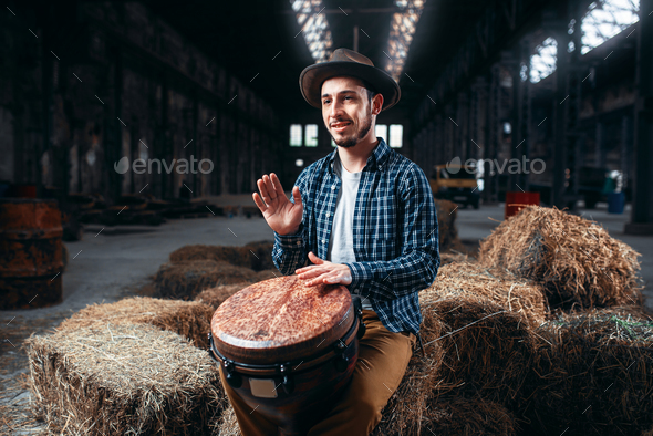 Young male drummer against african wooden drum - Stock Photo - Images