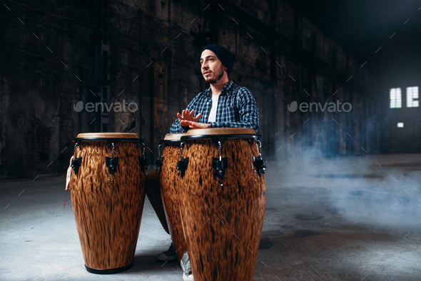Male drummer plays on wooden drums in factory shop - Stock Photo - Images