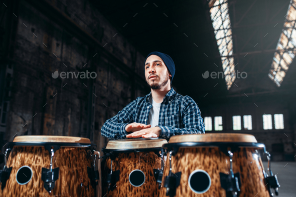 Male drummer plays on wooden drum - Stock Photo - Images