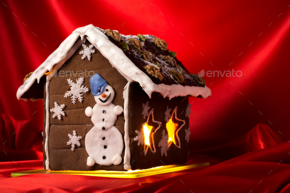 Christmas glazed gingerbread house with sugar snowman. - Stock Photo - Images