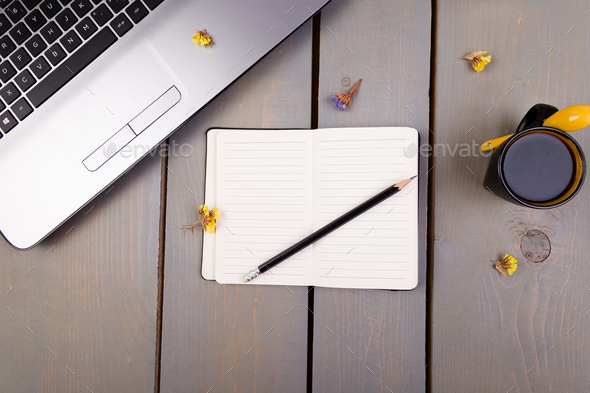 Notebook, coffee and flowers for female home or office workplace on wooden background. top view - Stock Photo - Images